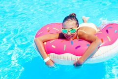 Tween girl in resort pool. Tween girl relaxing on the inflatable ring in resort pool in Thailand Royalty Free Stock Photo