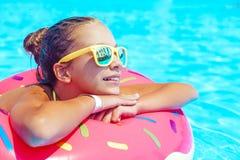 Tween girl in resort pool. Tween girl relaxing on the inflatable ring in resort pool in Thailand Royalty Free Stock Image