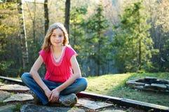 Tween girl sitting cross-legged. Twelve year old girl sitting cross-legged on a rock outdoors Stock Photo