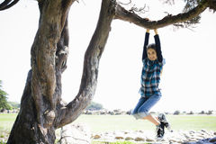Tween Girl Swinging From Tree Branch Royalty Free Stock Photos