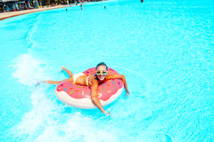 Tween girl in water park. Tween girl relaxing on the inflatable ring in water in the aqua park in Thailand Stock Photography