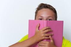 Tween jongen die zijn gezicht behandelen met het boek Royalty-vrije Stock Afbeelding