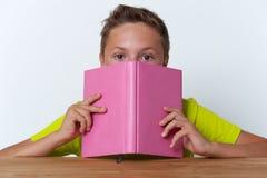 Tween jongen die zijn gezicht behandelen met het boek Stock Foto's