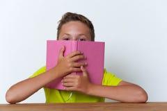 Tween jongen die zijn gezicht behandelen met het boek Stock Afbeeldingen