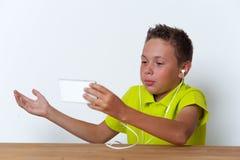 Tween jongen met smartphone en oortelefoons Stock Fotografie