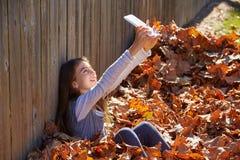 Tween kid girl selfie tablet pc in autumn leaves Stock Photography