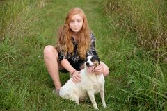 Tween long hair red head and dog Royalty Free Stock Photography