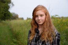 Tween long hair red head with green landscape Royalty Free Stock Images
