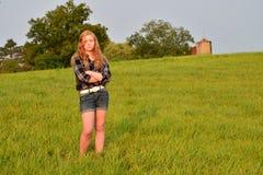 Tween long hair red head in open field Stock Photo
