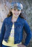 Tween-Mädchen, das auf Baum sich lehnt stockbild