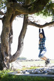 Tween-Mädchen, das vom Baum-Zweig schwingt Lizenzfreie Stockbilder