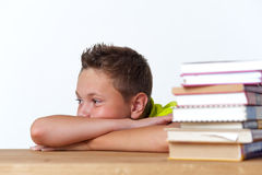 Tween pensive child sitting at table with books Stock Image
