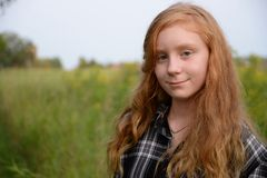 Tween red head in green field Royalty Free Stock Images