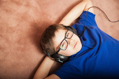 Tween relaxing with music. Portrait of a young boy wearing glasses and headphones listening to music. Plenty of copy space Stock Photos