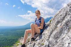 Tween tourist girl sitting on mountain cliff and looking at camera againt blue sky and summer landscape of valley. Hiking,. Travelling and wanderlust concept royalty free stock photos