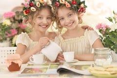 Tweenie girls  in wreaths with magazine Royalty Free Stock Photos