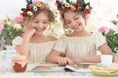 Tweenie girls  in wreaths with magazine Stock Image