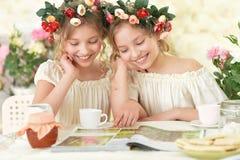 Tweeniemeisjes in kronen met tijdschrift Stock Foto's