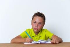 Tweenjunge, der am Tisch mit Übungsbuch sitzt Stockbild