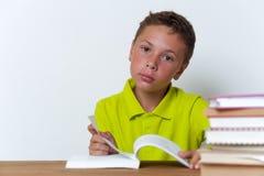 Tweenjunge, der am Tisch und am Lesebuch sitzt Stockfotos