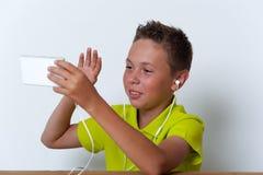 Tweenjunge mit Smartphone und Kopfhörern Lizenzfreies Stockbild