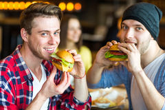 Tweepersoons het eten hamburger Het jonge meisje en de jonge mens houden burgers op handen stock foto's