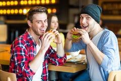 Tweepersoons het eten hamburger Het jonge meisje en de jonge mens houden burgers op handen stock afbeelding