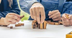 Tweepersoons men vrouwenarchitect trekt een plan, op groot blad van document bij bureau en bouwt modelhuis van houten blokkenbars stock foto