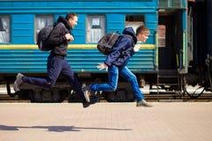 Tweepersoons met grote die zakken bij station in werking worden gesteld stock afbeelding