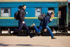 Tweepersoons met grote die zakken bij station in werking worden gesteld stock fotografie