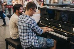 Tweepersoons spelend een openbare die piano in de zaal binnen St wordt geïnstalleerd Royalty-vrije Stock Fotografie