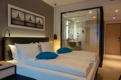 Tweepersoonsbed in een luxueuze hotelruimte stock afbeeldingen