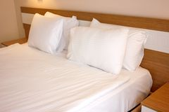 Tweepersoonsbed met witte linens, die op bedtijdslaap wordt voorbereid stock foto