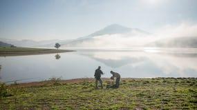 Tweepersoonstribune door meer anh alleen boom op het meer, zonsopgang bij mistige mountai, wolk op de hemel Royalty-vrije Stock Foto's