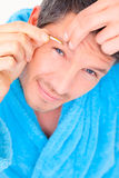 Tweeze man. Male cosmetic treatment removing hairs with tweezing Royalty Free Stock Images