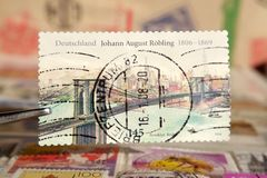 Tweezer holds postage stamp printed by Germany on topic Anniversaries, Shows Johann August. Robling Brooklyn Bridge, CIRCA 2006 royalty free stock photos