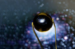 Tweezers holding a Little Glass ball reflecting the Milky Way Royalty Free Stock Photo