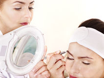 Tweezing eyebrow by beautician. Stock Photos