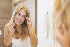 Tweezing eyebrows. Beautiful blonde woman tweezing eyebrows Royalty Free Stock Photos