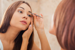 Tweezing eyebrows. Beautiful young woman tweezing her eyebrows while looking at the mirror Royalty Free Stock Photos