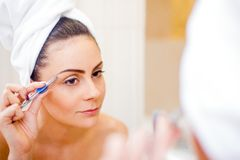 Tweezing eyebrows. Pretty woman tweezing her eyebrows in the mirror Royalty Free Stock Image