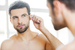 Tweezing his eyebrows. Handsome young man tweezing his eyebrows and looking at himself while standing in front of the mirror Royalty Free Stock Photo