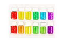 Twelve bottles of different colored aromatic oils Stock Images