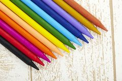 Twelve color pastel crayon  in box close up with woody texture backgrou. Nd Stock Images