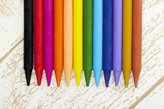 Twelve color pastel crayon  in box close up with woody texture backgrou Royalty Free Stock Images