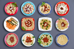 Twelve delicious pasta dishes. Top down view on twelve square and circular plates filled with various types of pasta topped with choice meats, fish, herbs Stock Photos