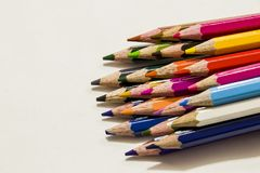 Colour pencils on white background. Twelve different Colour crayons and three erasers on white background Stock Images