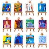 Twelve mini paintings on easels isolated on white Stock Images