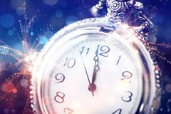 Twelve o`clock - new year`s eve. New Year`s at midnight - Old clock with stars snowflakes and holiday lights Stock Photo