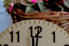 Twelve o'clock. Section of clock showing twelve o'clock, midday, noon or midnight with flowers in the background Stock Photo